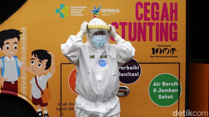Tenaga medis mendampingi orang tanpa gejala (OTG) menaiki bus sekolah di Puskesmas Kecamatan Jatinegara, Jakarta, Kamis (24/9/2020). Sejumlah unit bus sekolah kini dialihfungsikan menjadi kendaraan untuk mengantar pasien Covid-19 berstatus OTG dari puskesmas ke RS Darurat Wisma Atlet seiring meningkatnya kasus baru virus corona di Jakarta.
