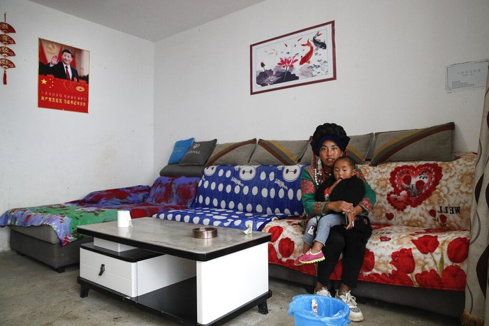 A Yi woman watches new village houses decorated with colourful paintings which were built by the Chinese government for the ethnic minority members in Ganluo county, southwest China's Sichuan province on Sept. 10, 2020. China's ruling Communist Party says its initiatives have helped to lift millions of people out of poverty. Yi ethnic minority members were moved out of their mountain villages in China's southwest and into the newly built town in an anti-poverty initiative. (AP Photo/Andy Wong)