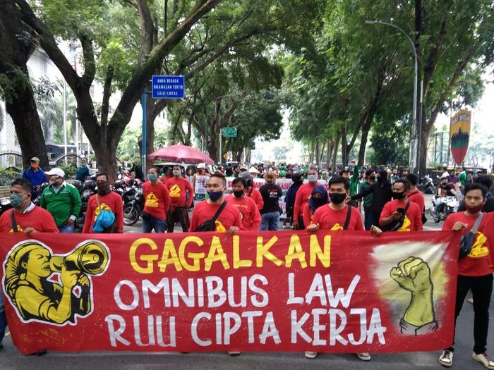 Massa buruh menggelar demonstrasi di depan kantor DPRD Sumut. Mereka menolak RUU Cipta Kerja