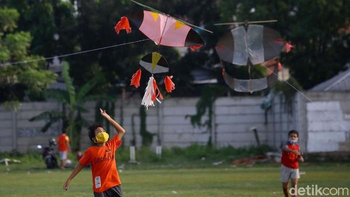 Sejumlah anak bermain layang-layang di kawasan Jakarta Barat. Anak-anak itu tampak mengenakan masker saat bermain layang-layang di lapangan terbuka.
