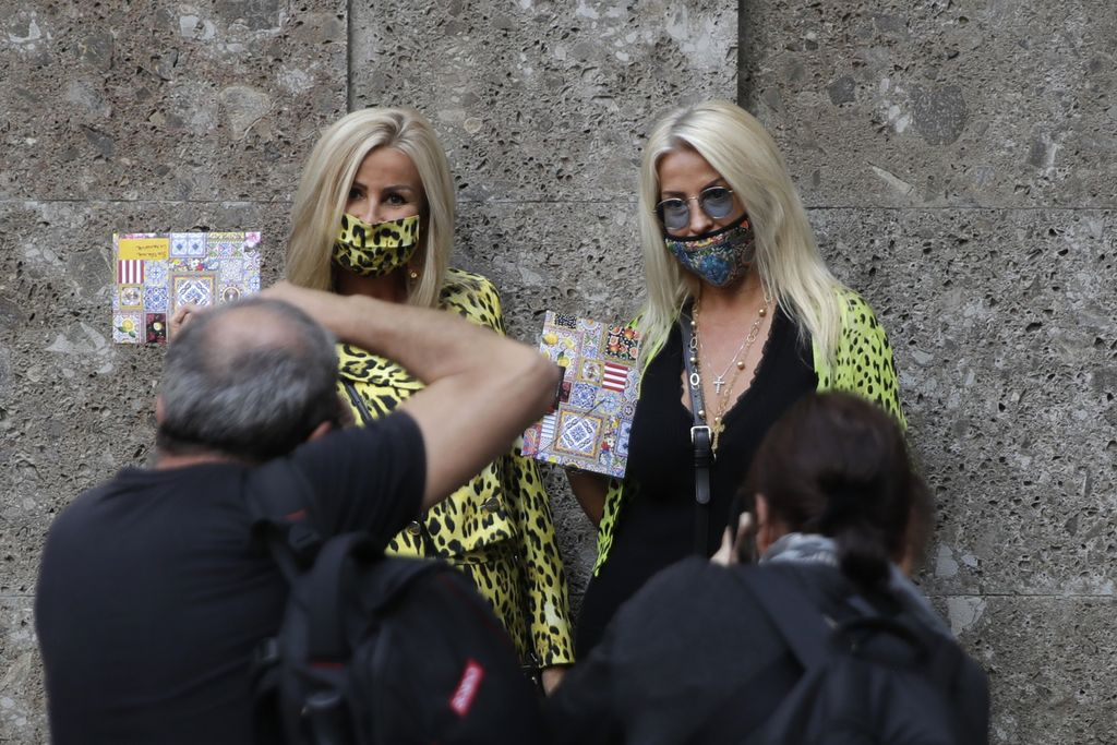 Two guests pose for photographers prior to the Dolce & Gabbana 2021 women's spring-summer ready-to-wear collection during the Milan's fashion week in Milan, Italy, Wednesday, Sept. 23, 2020. (AP Photo/Luca Bruno)
