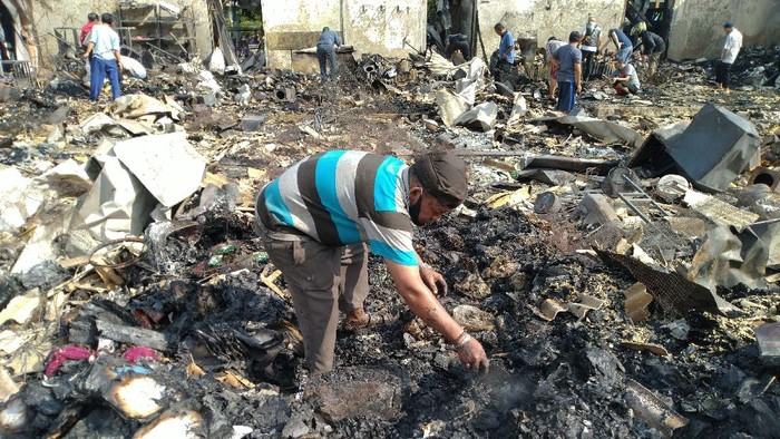 Pedagang Pasar Cempaka Putih mengais di tumpukan puing sisa kebakaran