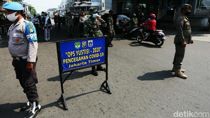 Petugas gabungan menggelar Operasi Yustisi di Terminal Kampung Melayu, Jakarta Timur, Kamis (24/09/2020). Warga yang melanggar dihukum mengecat trotoar.