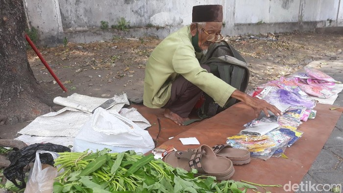 Dalimin (80) jualan kangkung, sandal dan masker di Alun-alun Kidul Keraton Kasunanan Surakarta, Jumat (25/9/2020).