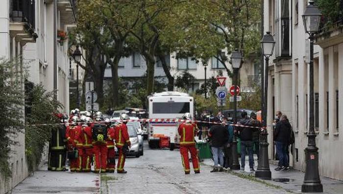 Petugas pemadam kebakaran berkumpul di lokasi penusukan dekat eks kantor majalah Charlie Hebdo.