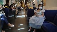 Tampak sejumlah wisatawan mengenakan masker saat menaiki kereta yang menuju ke Disneyland Hong Kong.