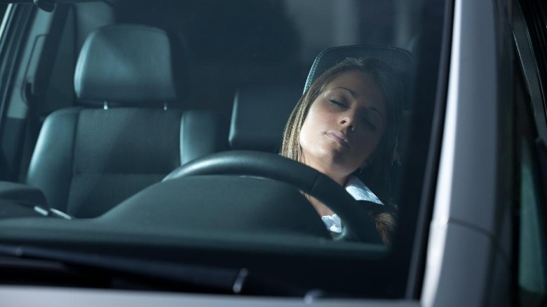 Exhausted young woman sleeping in a car with eyes closed.