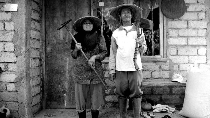 Paini (42, kanan) dan anaknya Putra (14, kiri) berpose di depan rumahnya di kawasan Transmigrasi Sungai Bermas, Siulak, Kerinci, Jambi.