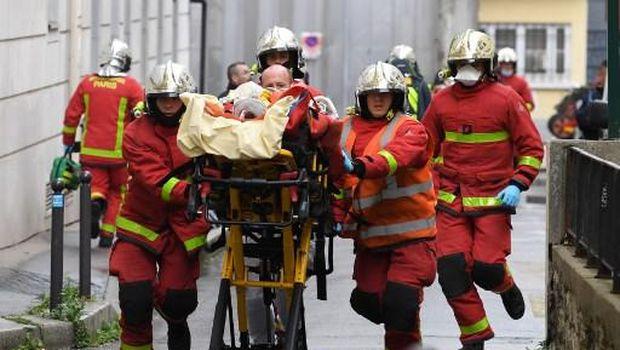 Petugas pemadam kebakaran Paris membawa korban penusukan di dekat eks kantor majalah Charlie Hebdo. (Photo by Alain JOCARD / AFP)
