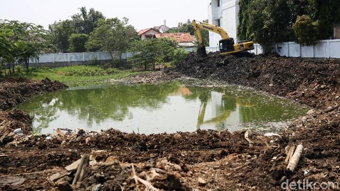 Petugas dari Dinas Sumber Daya Air menggunakan kendaraan alat berat saat menyelesaikan pembuatan Waduk Pilar Jati di Cipinang Melayu, Kecamatan Makassar, Jakarta Timur. Pemprov DKI Jakarta membuat waduk diharapkan dapat mencegah banjir yang kerap melanda kawasan Cipinang Melayu.