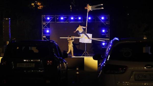Anggota sirkus tampil saat drive-in sirkus di tempat parkir di Seoul, Korea Selatan. AP Photo/Ahn Young-joon