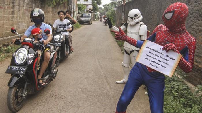 Beragam upaya dilakukan sejumlah orang untuk mencari rezeki di masa pandemi. Salah satunya dengan menggunakan kostum super hero untuk menarik perhatian warga.