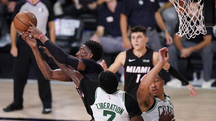 Miami Heats Bam Adebayo, left, battles for a rebound along with Boston Celtics Jaylen Brown (7) and teammate Grant Williams (12) during the second half of an NBA conference final playoff basketball game Sunday, Sept. 27, 2020, in Lake Buena Vista, Fla. (AP Photo/Mark J. Terrill)