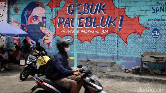 Warga melintas di depan mural bertemakan lawan wabah Covid-19 di Pasar Serangan, Yogyakarta, Senin (28/09/2020). Gambar mural tersebut mengingatkan warga untuk melawan wabah Covid-19 dengan menerapkan 3M protokol kesehatan Covid-19 yaitu dengan mencuci tangan, menggunakan masker dan menjaga jarak fisik.