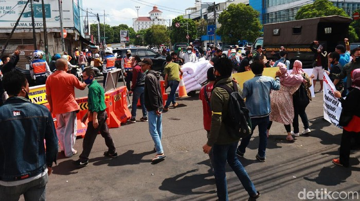 Ratusan pedagang Pasar Baru Bandung turun ke jalan dan melakukan aksi protes dengan kebijakan Pemerintah Kota (Pemkot) Bandung yang mengeluarkan kebijakan buka tutup jalan di Jalan Suniaraja-Otista. Pantauan detikcom, Senin (28/92020) water barier yang menutup jalan tersebut dibuka paksa dan dipindahkan oleh para pedagang ke pinggir jalan.