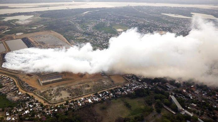 Residents commute to work through the smoke coming from a fire at the capital city's main landfill in the poor Bañado Sur neighborhood in Asuncion, Paraguay, Monday, Sept. 28, 2020. The fire began Saturday night and it has been burning ever since without firefighters been able to put it out. (AP Photo/Jorge Saenz)