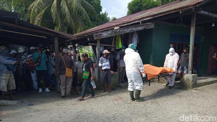 Jenazah pria di Timika dievakuasi Tim COVID-19 RSUD Mimika yang menggunakan APD lengkap (Saiman/detikcom)