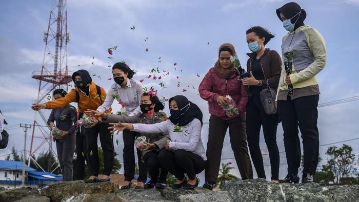 Seorang ibu menaburkan bunga ke laut di bekas lokasi tsunami, di Pantai Teluk Palu, Sulawesi tengah, Senin (28/9/2020).  Sejumlah keluarga korban mengenang kembali persitiwa yang terjadi pada 28 September 2018 lalu itu dengan mendatangi lokasi bencana dan berdoa untuk keselamatan korban. ANTARAFOTO/Basri Marzuki/hp.
