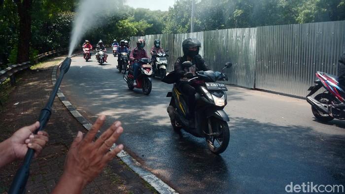 Kendaraan truk berplat nomor wilayah Bogor disemprotkan dengan cairan probiotik untuk mencegah penyebaran virus saat melintas di jalan perbatasan antar kota Depok dan Jakarta