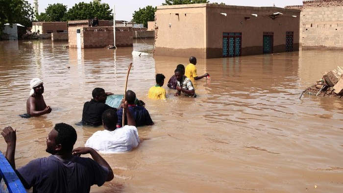 A Sudanese man stands in flood water, after torrential rain lead to landslides and flash floods, in the town of Umm Dawan Ban, southeast of the capital Khartoum on August 2, 2020. (Photo by ASHRAF SHAZLY / AFP)