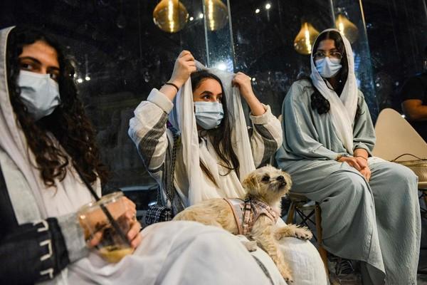 Para wanita-wanita ini asyik nongkrong bersama anjing-anjing peliharaan mereka di Barking Lot, Cafe Anjing pertama di Arab Saudi.