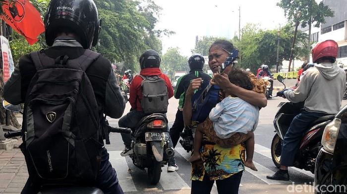 Mengamen kerap dilakukan sejumlah orang untuk bertahan hidup di tengah kerasnya Ibu Kota. Tak jarang sejumlah ibu membawa serta anaknya saat mengamen.