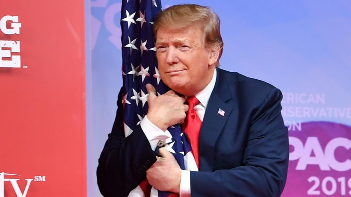 US President Donald Trump hugs the US flag as he arrives to speak at the annual Conservative Political Action Conference (CPAC) in National Harbor, Maryland, on March 2, 2019. (Photo by NICHOLAS KAMM / AFP) / ALTERNATIVE CROP