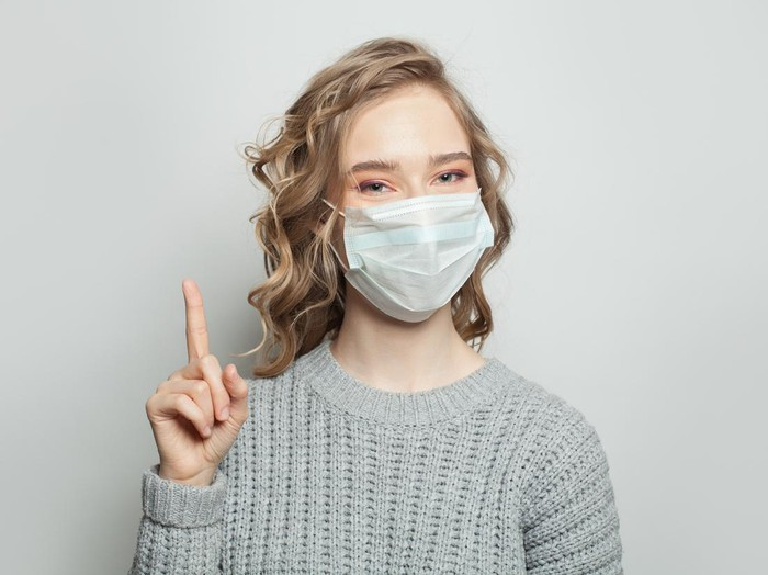 Pretty woman wearing a medical mask and pointing finger up on white background