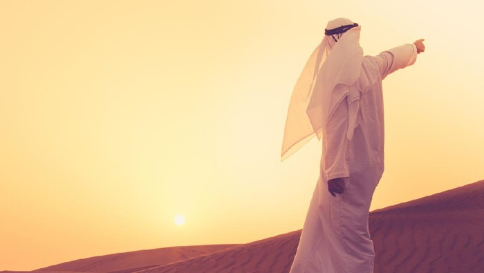 An Arab standing at the sand dunes of Dubai and aiming towards the horizon.
