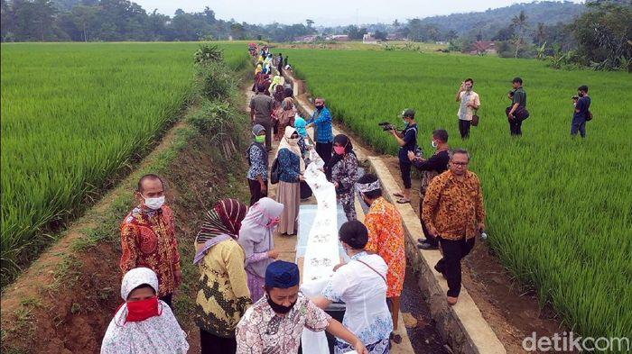 Memperingati hari batik nasional sejumlah warga di Desa Agro Eduwisata Parungseah, Kabupaten Sukabumi membatik massal dan membentangkannya di area pesawahan.