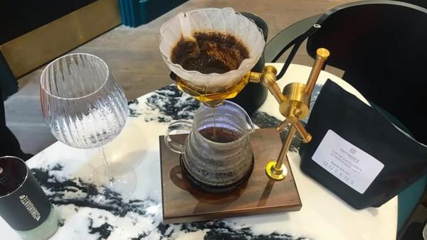 Menu kopi yang dimaksud, digiling dan diseduh oleh barista pribadi Anda. Biji Ethiopian Cup of Excellence Queens Coffee disajikan dalam gelas anggur kristal dan porsinya cukup untuk dua gelas.