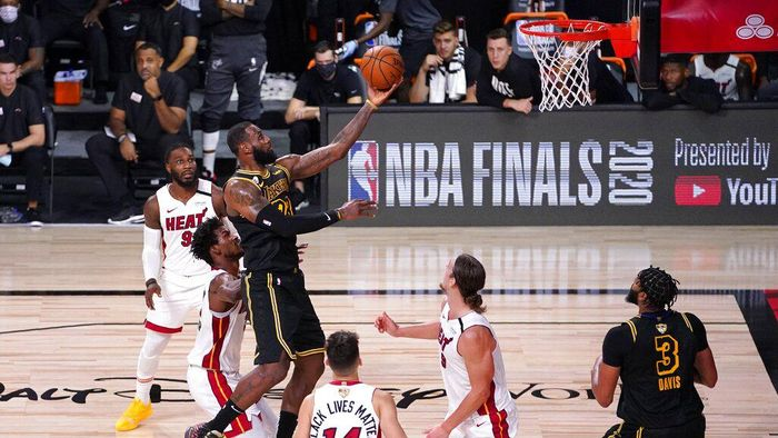 Los Angeles Lakers forward LeBron James (23) goes up for a shot between Miami Heats Jimmy Butler, center left, Tyler Herro (14), and Kelly Olynyk (9) during the second half of Game 2 of basketballs NBA Finals, Friday, Oct. 2, 2020, in Lake Buena Vista, Fla. (AP Photo/Mark J. Terrill)
