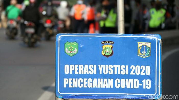Polisi melakukan Operasi Yustisi untuk penegakan penerapan protokol kesehatan. Polisi bersenjata laras panjang terlihat berjaga dalam operasi tersebut.