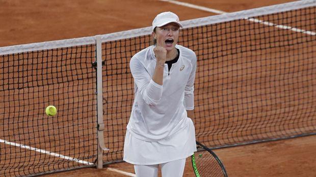 Poland's Iga Swiatek celebrates winning as Romania's Simona Halep's return missed, ball at left, in the fourth round match of the French Open tennis tournament at the Roland Garros stadium in Paris, France, Sunday, Oct. 4, 2020. (AP Photo/Alessandra Tarantino)