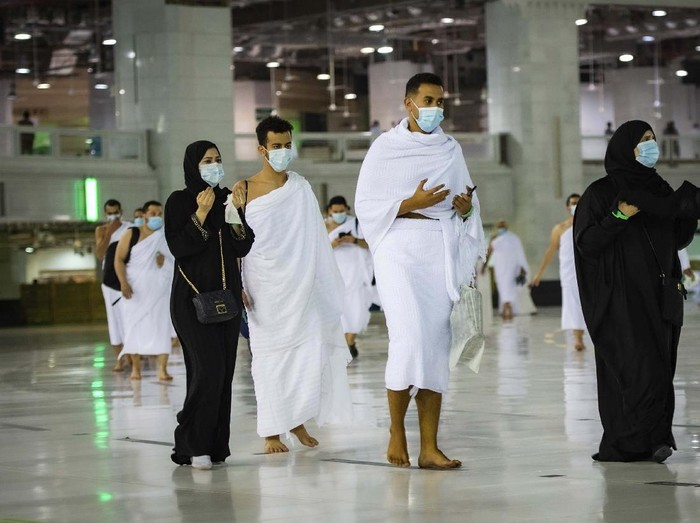 CLARIFIES THAT THE UMRAH PILGRIMAGE CAN BE UNDERTAKEN AT ANY TIME OF THE YEAR -- In this photo released by Saudi Ministry of Hajj and Umrah, Muslims practice social distancing while praying around the Kaaba, the cubic building at the Grand Mosque during the first day umrah pilgrimages were allowed to restart, in the Muslim holy city of Mecca, Saudi Arabia, Sunday, Oct. 4, 2020. The umrah pilgrimage, or smaller pilgrimage, can be undertaken at any time of the year. A very small, limited number of people donning the white terrycloth garment symbolic of the Muslim pilgrimage circled Islams holiest site in Mecca on Sunday after Saudi Arabia lifted coronavirus restrictions that had been in place for months. (Saudi Ministry of Hajj and Umrah via AP)