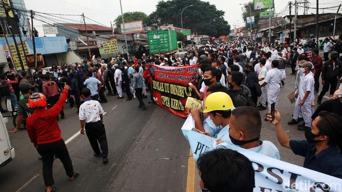 Para pekerja pabrik  melakukan aksi unjuk rasa dengan berjalan kaki di Jl Gatot Subroto, Jatiuwung, Kota Tangerang, Banten, Selasa (06/10/2020). Akibatnya, arus lalu-lintas sempat tersendat Karena jalan dikuasai massa. Unjuk rasa terkait pengesahan UU Cipta Karya oleh DPR RI
