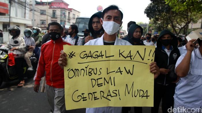Para pekerja pabrik  melakukan aksi unjuk rasa dengan berjalan kaki di Jl Gatot Subroto, Jatiuwuhg, Kota Tangerang, Banten, Selasa (06/10/2020. Unjuk rasa terkait pengesahan UU Cipta Karya oleh DPR RI.