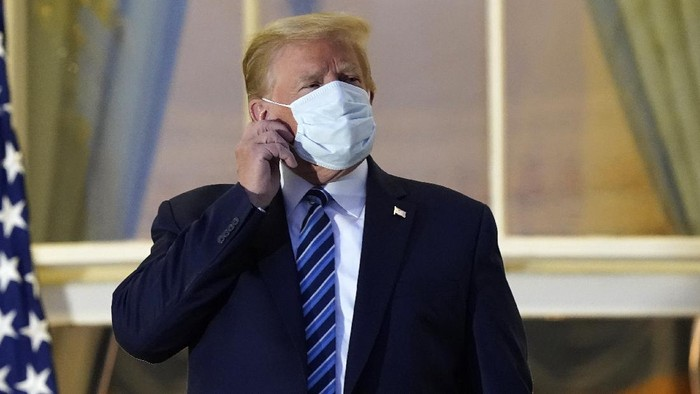 President Donald Trump removes his mask as he stands on the balcony outside of the Blue Room as returns to the White House Monday, Oct. 5, 2020, in Washington, after leaving Walter Reed National Military Medical Center, in Bethesda, Md. Trump announced he tested positive for COVID-19 on Oct. 2. (AP Photo/Alex Brandon)
