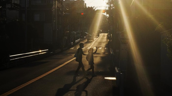 A child and her guardian walk across the street as they were silhouetted in the late afternoon sunlight Monday, Oct. 5, 2020, in Yokohama,Japan. (AP Photo/Kiichiro Sato)