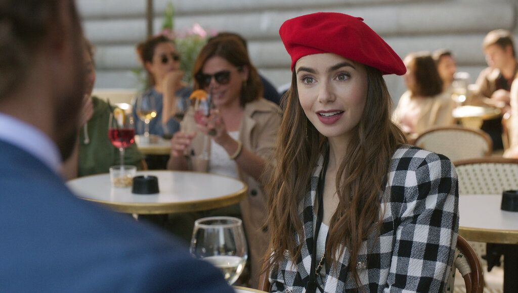 This image released by Netflix shows William Abadie, left, and Lily Collins in a scene from the series