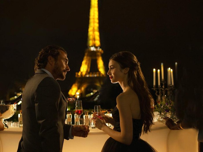 This image released by Netflix shows William Abadie, left, and Lily Collins in a scene from the series Emily in Paris, premiering on Friday. (Carole Bethuel/Netflix via AP)