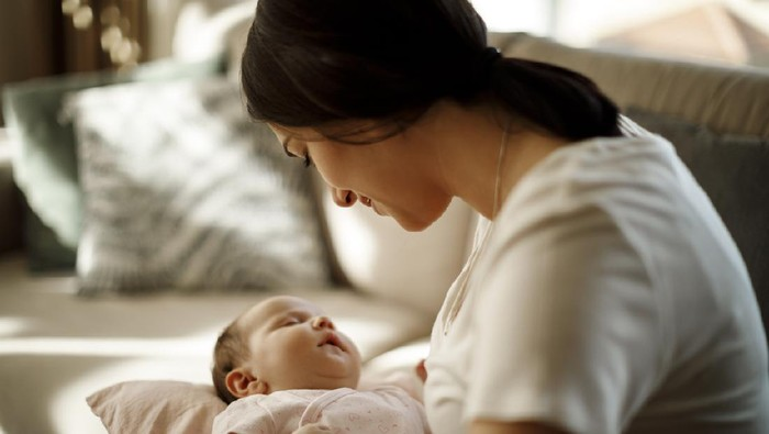 Mother holding her sleeping baby girl