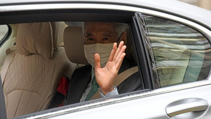Singapores Prime Minister Lee Hsien Loong waves as he arrives in a car at the High Court in Singapore on October 6, 2020. (Photo by ROSLAN RAHMAN / AFP)