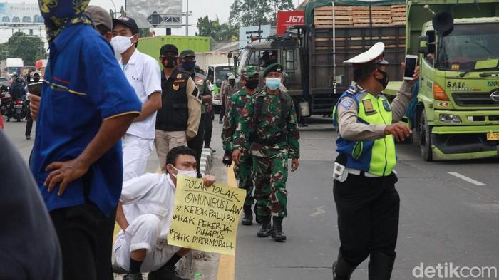 Aparat kepolisian dibantu TNI bersinergi mengamankan demo buruh di Jl Gatot Subroto, Kota Tangerang, Banten, Selasa (6/10/2020).