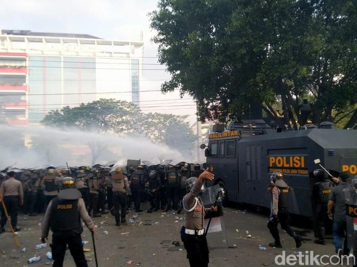 Aksi demo tolak UU Cipta Kerja di Gedung DPRD Jawa Tengah diwarnai aksi lempar botol hingga batu. Polisi pun tembakkan gas air mata ke arah massa demonstran.