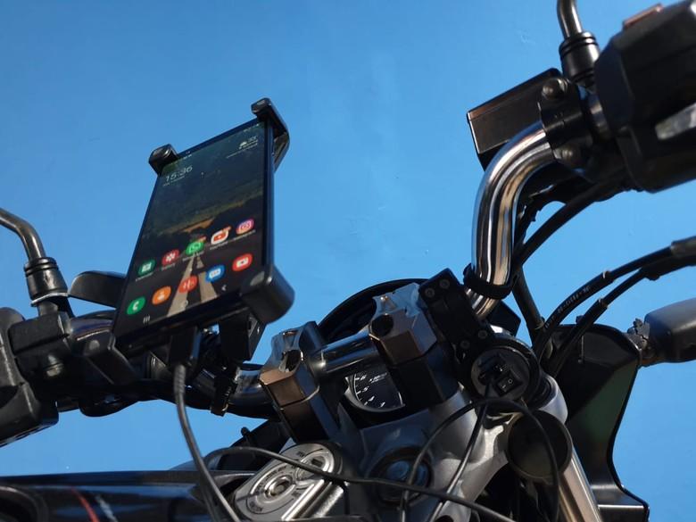 Ilustrasi ngecas handphone di motor