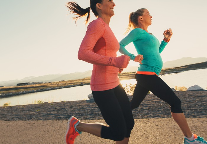 Two female runners in pink and blue athletic shirts are training for their next race. These women enjoy running at sunset in the evening together as friends on the trails through. Running is their way of staying active and healthy.