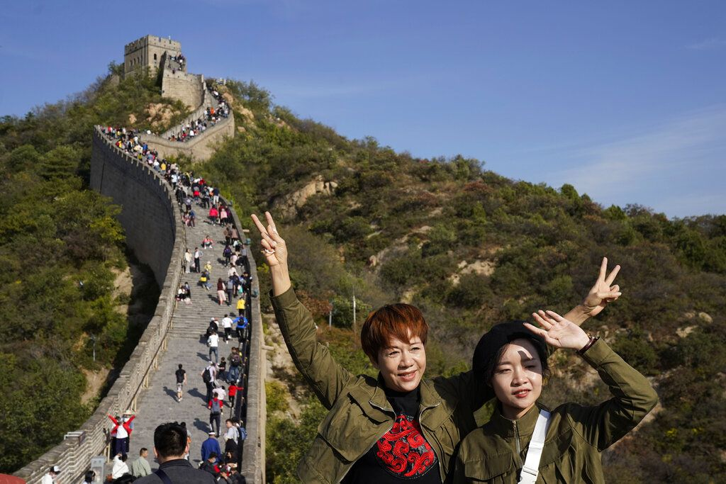 Tourists pose for photos along a stretch of the Badaling Great Wall of China on the outskirts of Beijing, Tuesday, Oct. 6, 2020. Chinese tourists took 425 million domestic trips in the first half of the eight-day National Day holiday, generating $45.9 billion in tourism revenue, according to China's ministry of culture and tourism. The holiday this year, which coincides with the Mid-Autumn Festival, will be a litmus test of whether China's tourism industry can bounce back after being battered by COVID-19. (AP Photo/Ng Han Guan)