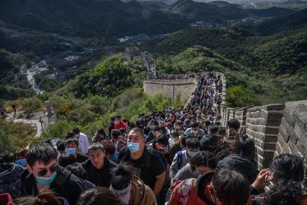 Akan tetapi dengan adanya pembatasan perjalanan, pariwisata domestik pun melonjak. Salah satu destinasi yang dikunjungi adalah Tembok Besar China. Kevin Frayer/Getty Images