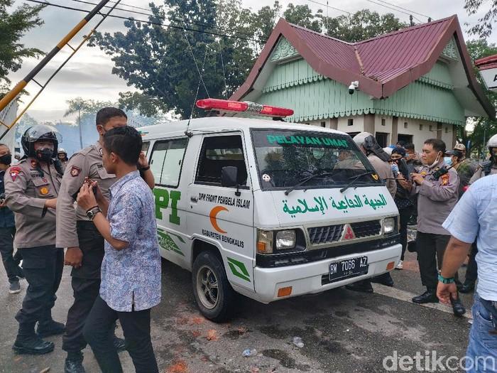 Ambulans bertuliskan FPI ditahan aparat karena menerobos kerumunan massa yang demo tolak Omnibus Law di DPRD Riau. Dua orang diamankan (Chaidir Tanjung/detikcom)